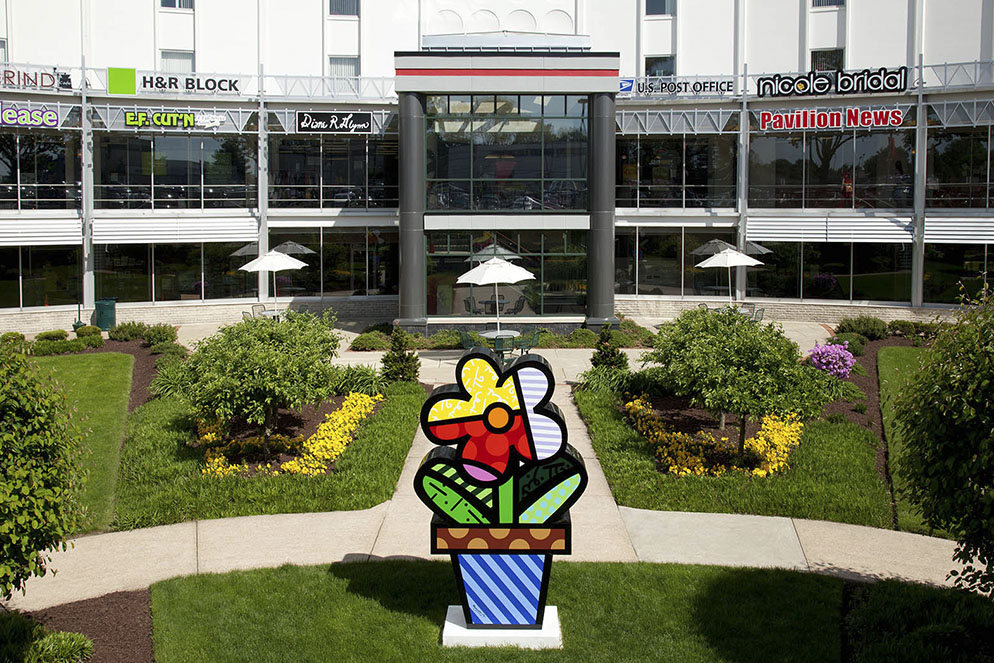 Front entrance of Galman Pavilion building showing a colorful flower sculpture in the courtyard